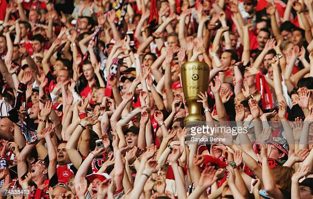 A replica mascot of the German Cup is held aloft amongst the crowd of Nuremberg fans prior to the DFB German Cup Final football match between VfB...