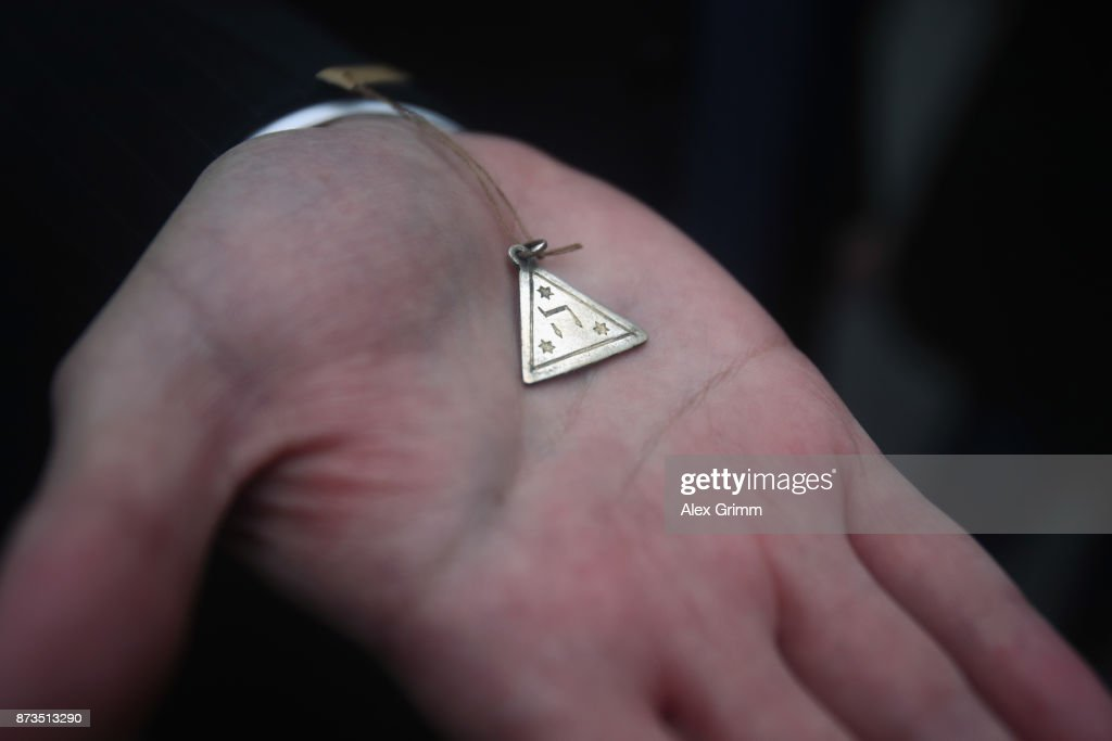 A replica of the amulet is shown after German artist Gunter Demnig layed four 'stumbling stones' to commemorate Jewish schoolgirl and Holocaust victim Karolina Cohn and her family outside the building where they once lived on November 13, 2017 in Frankfurt, Germany. Karolina's fate came to light after Israeli archeologists digging at the former World War II Sobibor concentration camp found an amulet inscribed with Karolina's birthdate and birthplace, which helped them to confirm that she and her family were killed there. The Nazis deported Karolina, then 12, and her family to Minsk in 1941, though the rest of their journey had been unknown until now. Approximately 30 members of the Cohn family came from the United States, Israel, Japan and Canada to attend today's ceremonies. 'Stumbling stones,' in German called 'Stolpersteine,' are commemorative cobblestones affixed with a brass plate with the names of victims laid in the sidewalks outside the former residences of Jews in Germany killed in the Holocaust.