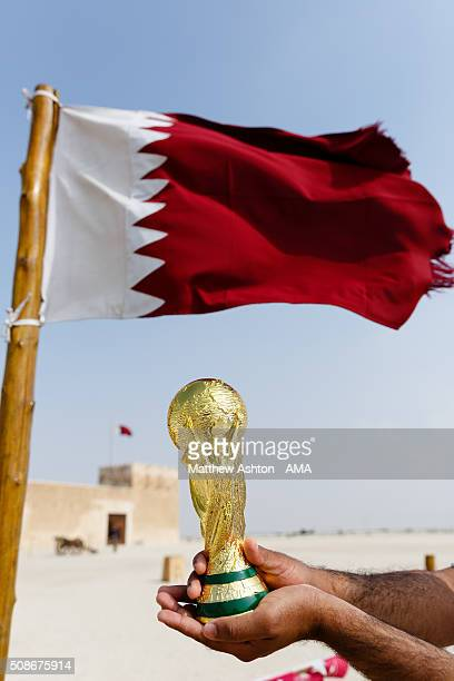 A replica of the FIFA World Cup Trophy in front of the maroon and white coloured flag of Qatar at the Al Zubarah Fort a UNESCO World Heritage Site in...