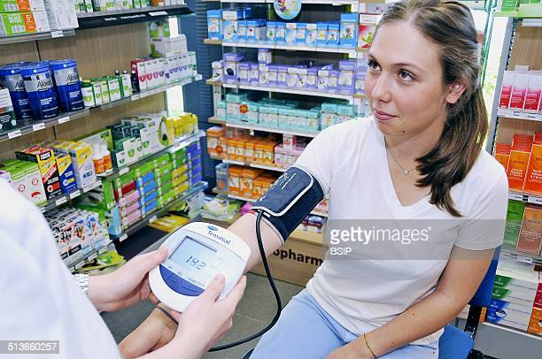 Reportage in a chemist's in FontenaysousBois France The chemist measures a client's blood pressure