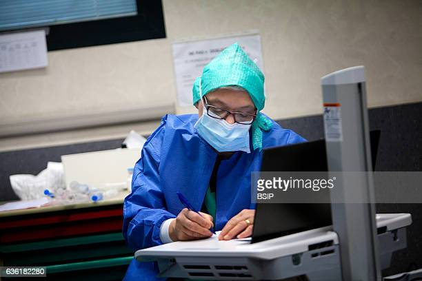 Reportage in an operating theatre during a hysterectomy using the da Vinci robot¬ The anaesthetist nurse fills in information sheets
