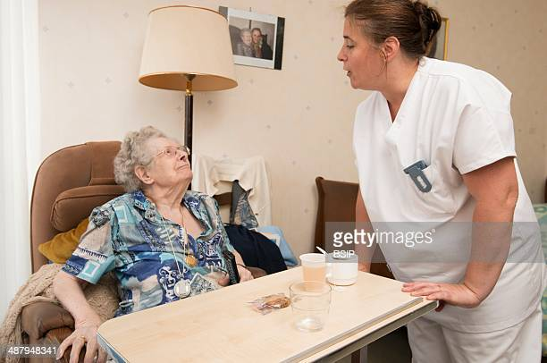 Reportage in the « Accueil » nursing home in Lille France An auxiliary nurse hands out snacks in the residents bedrooms