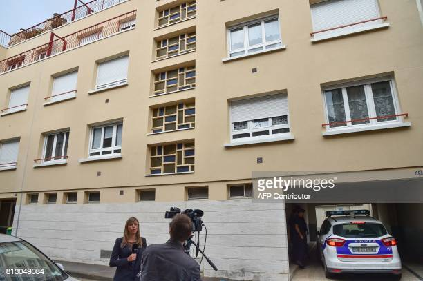 A reporter broadcasts live as he police car drives through the porch of the appartments building on July 12 where late French magistrate JeanMichel...
