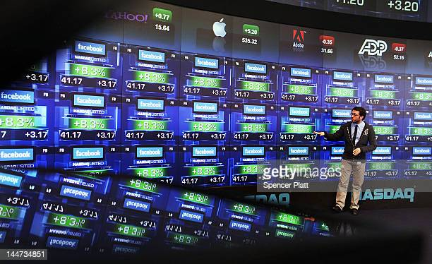 A reporter for French TV stands onstage as the share price of newly debuted Facebook stock is viewed at the Nasdaq stock market moments after it went...