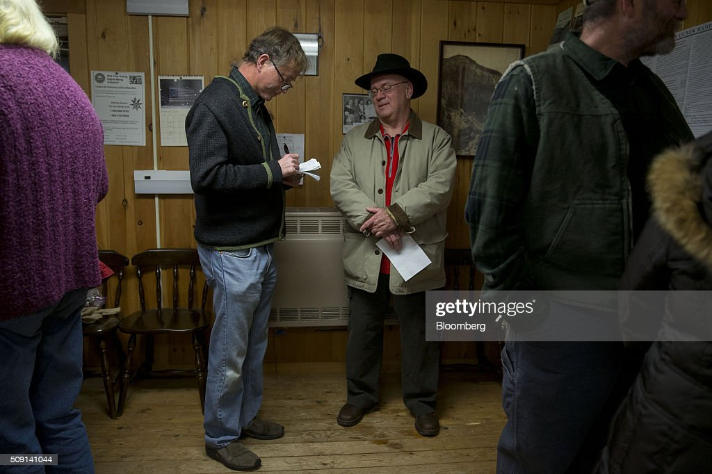 A reporter for the Conway Daily Sun, center left, interviews a resident after casting his vote at the town hall polling site during the New Hampshire presidential primary election in Harts Location, New Hampshire, U.S., on Tuesday, Feb. 9, 2016. According to the New Hampshire Secretary of State's office, the state has 383,834 voters who haven't declared a party affiliation, compared to 260,896 registered Republicans and 229,202 Democrats. Photographer: Andrew Harrer/Bloomberg via Getty Images