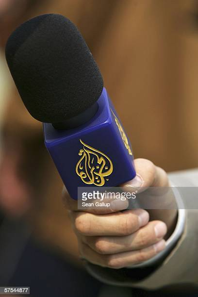 A reporter from the Arabic television channel AlJazeera holds a microphone during an interview after a friendly soccer match between Muslim and...