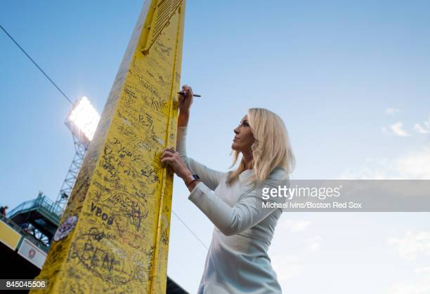NESN reporter Guerin Austin signs the right field 'Pesky Pole' before a game between the Boston Red Sox and the Tampa Bay Rays at Fenway Park on...