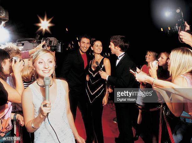 TV Reporter Holding a Microphone Standing in Front of an Actress and Actor Being Interviewed on a Red Carpet by a Crowd of Fans