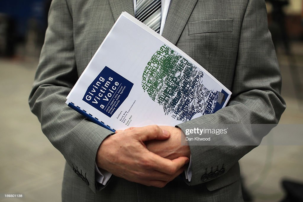 A reporter holds a copy of a report into the sexual allegations of the late TV star, Jimmy Savile outside New Scotland Yard on January 11, 2013 in London, England. The report by the Metropolitan police and NSPCC on Jimmy Savile gives details the scale of his sexual abuse of children from 1955 to 2009.