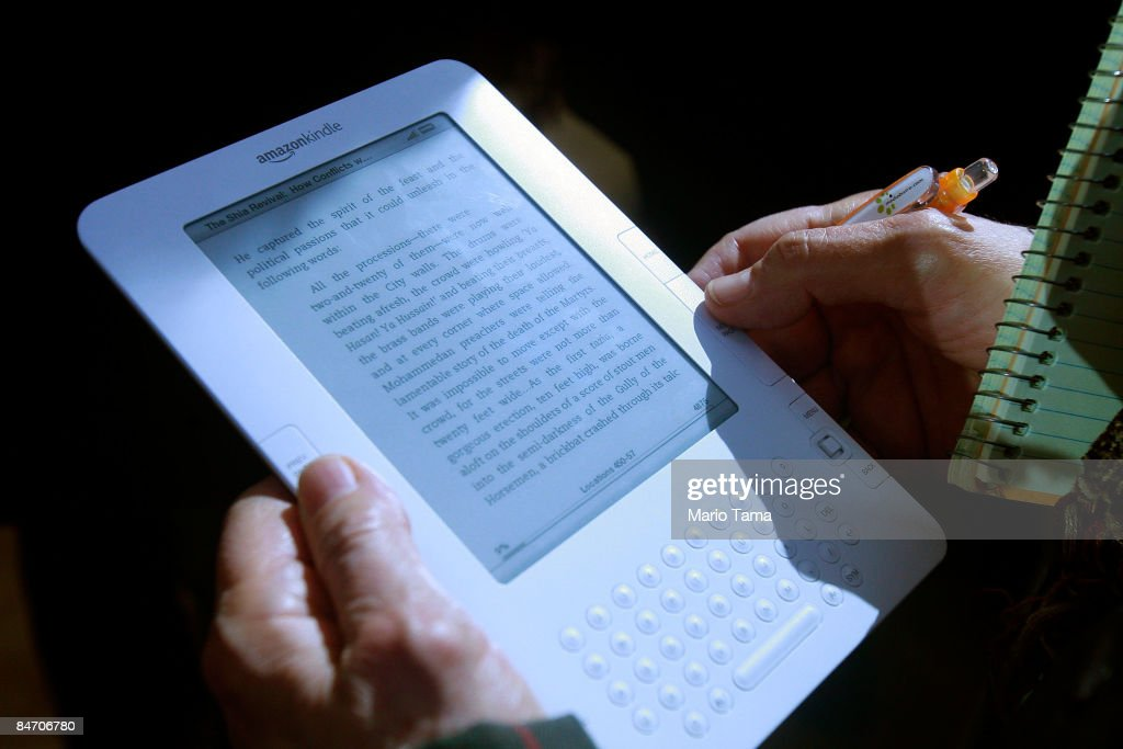 A reporter holds the new Amazon Kindle 2.0 at an unveiling event at the Morgan Library & Museum February 9, 2009 in New York City. The updated electronic reading device is slimmer with new syncing technology and longer battery life and will begin shipping February 24th.