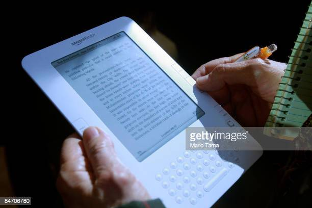 A reporter holds the new Amazon Kindle 20 at an unveiling event at the Morgan Library Museum February 9 2009 in New York City The updated electronic...