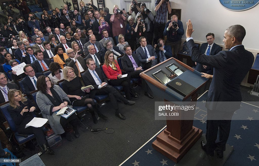 A reporter holds up a sign to ask a question, as US President Barack Obama holds a year-end press conference in the Brady Press Briefing Room of the White House in Washington, DC, December 16, 2016. Obama on Friday warned his successor Donald Trump against antagonizing China by reaching out to Taiwan, saying he could risk a 'very significant' response if he upends decades of diplomatic tradition. / AFP / SAUL