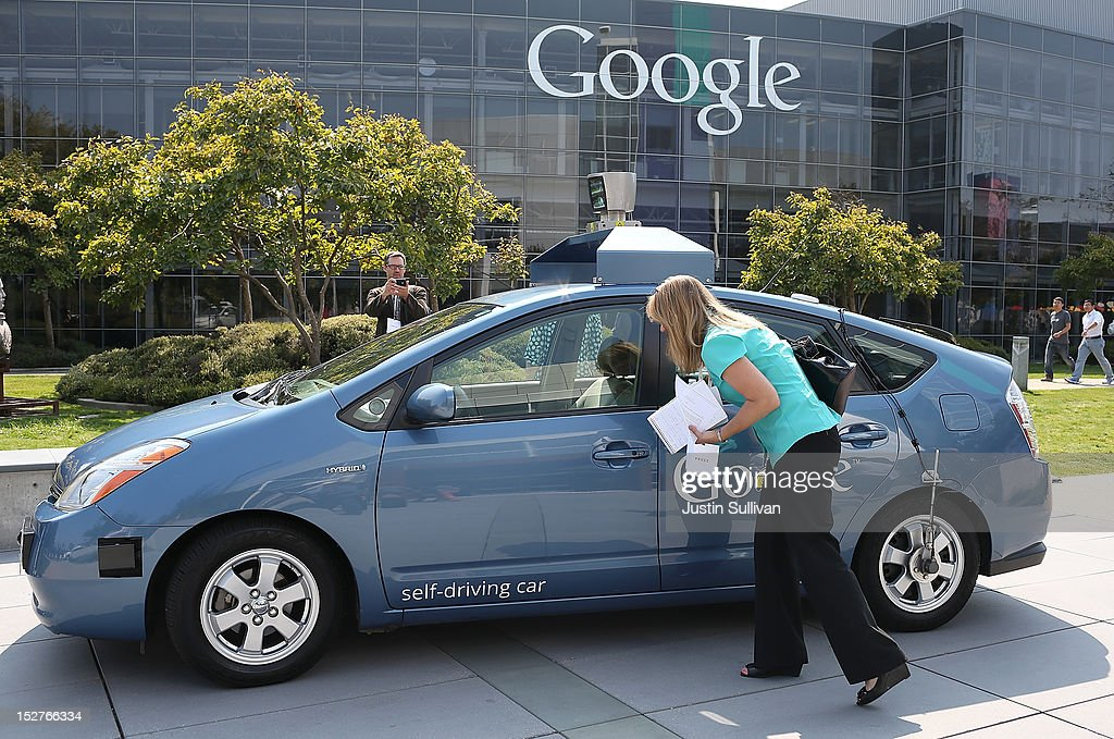 A reporter looks at a Google self-driving car at the Google headquarters on September 25, 2012 in Mountain View, California. California Gov. Jerry Brown signed State Senate Bill 1298 that allows driverless cars to operate on public roads for testing purposes. The bill also calls for the Department of Motor Vehicles to adopt regulations that govern licensing, bonding, testing and operation of the driverless vehicles before January 2015.