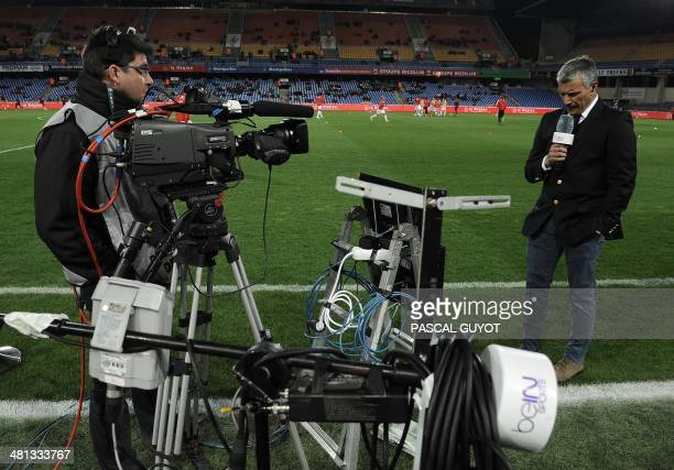 A reporter of Qatar's AlJazeera owned television channel BeIN Sports is filmed during a live broadcast prior to the French L1 football match...