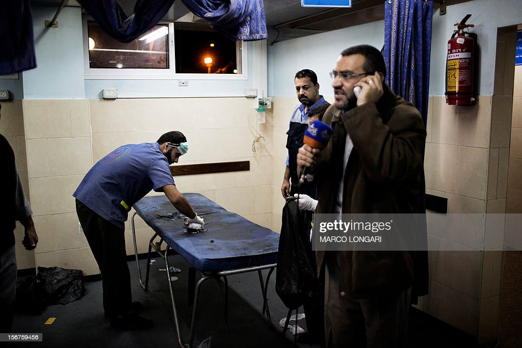 A reporter of the Hamas-owned Al-Aqsa TV station broadcasts live from the al-Shifa hospital in Gaza City while a nurse cleans the stretcher that brought the body of one of the two al-Aqsa reporters killed in an Israeli airstrike on November 20, 2012. Two cameramen from Hamas-owned Al-Aqsa TV were among six people killed in Israeli air raids on the Gaza Strip, raising Tuesday's death toll to 20, a Hamas spokesman said. AFP PHOTO/MARCO LONGARI