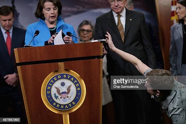 A reporter places her iPhone on the podium as Sen Dianne Feinstein delivers remarks during a news conference about Democratic legislative proposals...