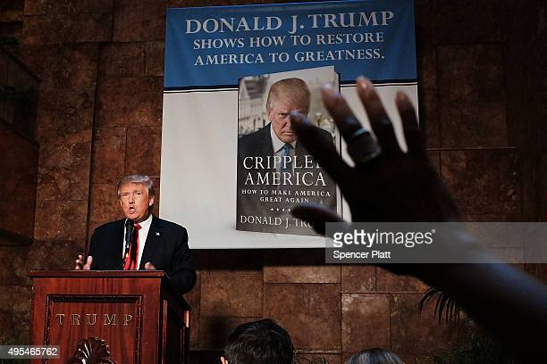 A reporter raises her hand at a news conference with Republican presidential candidate Donald Trump before a public signing for his new book...
