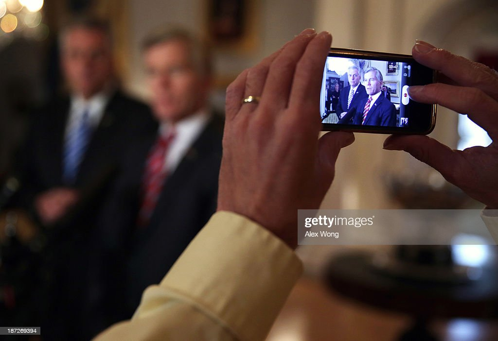A reporter records as incumbent Virginia Governor <a gi-track='captionPersonalityLinkClicked' href=/galleries/search?phrase=Bob+McDonnell&family=editorial&specificpeople=6369061 ng-click='$event.stopPropagation()'>Bob McDonnell</a> (R) and Governor-elect <a gi-track='captionPersonalityLinkClicked' href=/galleries/search?phrase=Terry+McAuliffe&family=editorial&specificpeople=206776 ng-click='$event.stopPropagation()'>Terry McAuliffe</a> speak to members of the media at the Executive Mansion November 7, 2013 in Richmond, Virginia. Governor McDonnell hosted Governor-elect McAuliffe, who will succeed him as the next governor of the commonwealth, with a private lunch, and followed with a joint press availability to answer questions from the media.