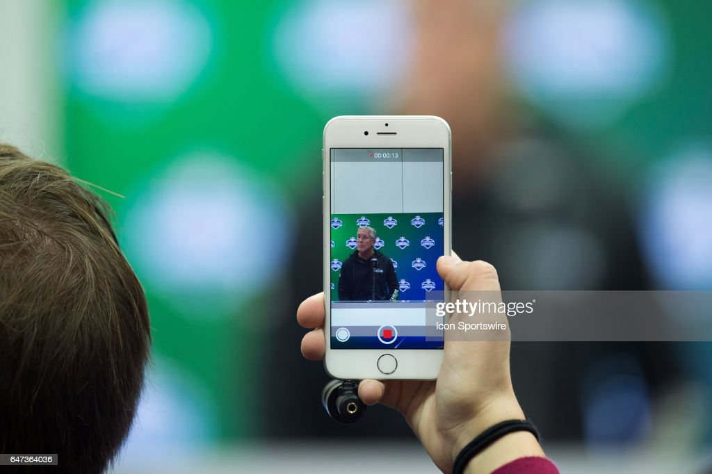 A reporter records Seattle Seahawks head coach Pete Carroll as he answers questions from the podium during the NFL Scouting Combine on March 2, 2017 at Lucas Oil Stadium in Indianapolis, IN.