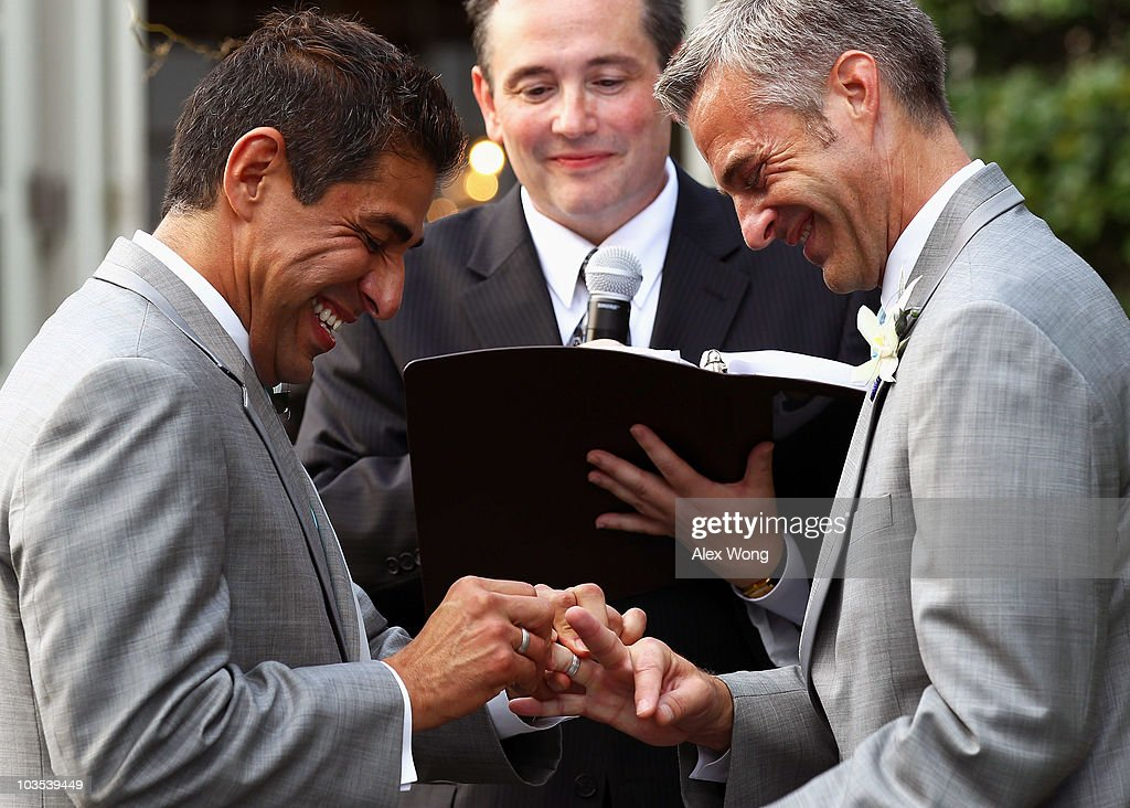 TV reporter Roby Chavez exchanges rings with his partner Chris Roe during their wedding ceremony officiated by Rev Dwayne Johnson of Metropolitan...