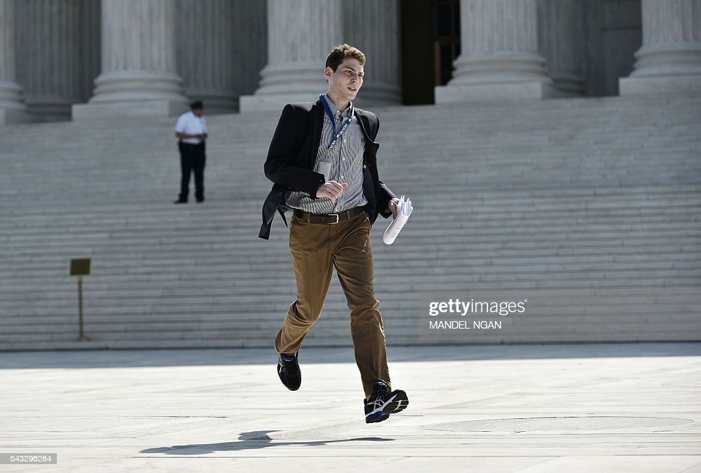 A reporter runs out of the US Supreme Court after the Court struck down a Texas law placing restrictions on abortion clinics, outside of the Supreme Court on June 27, 2016 in Washington, DC. In a case with far-reaching implications for millions of women across the United States, the court ruled 5-3 to strike down measures which activists say have forced more than half of Texas's abortion clinics to close. / AFP / Mandel Ngan