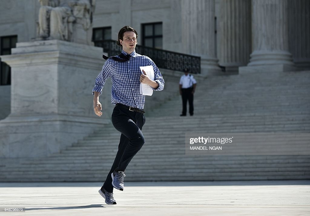 A reporter runs out of the US Supreme Court after the Court struck down a Texas law placing restrictions on abortion clinics, outside of the Supreme Court on June 27, 2016 in Washington, DC. In a case with far-reaching implications for millions of women across the United States, the court ruled 5-3 to strike down measures which activists say have forced more than half of Texas's abortion clinics to close. / AFP / MANDEL