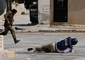 AFP reporter Sammy Ketz hits the ground as a Syrian soldier runs past during snipper fire in the ancient Christian Syrian town of Maalula on...