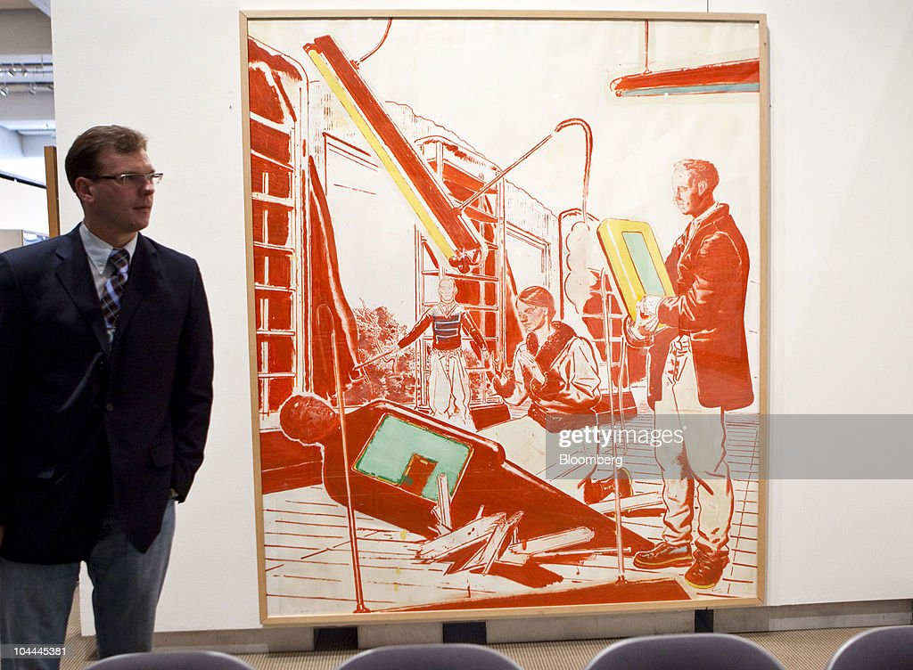 A reporter stands in front of a painting by Neo Rauch titled 'Einbruch' during an auction of Lehman Brother's artwork collection at Sotheby's in New York, U.S., on Saturday, Sept. 25, 2010. Artworks being auctioned from the collection of Lehman Brothers Holdings Inc. may raise another $16 million for its creditors as collectors and souvenir hunters snap up remains of the collapsed bank. Photographer: Ramin Talaie/Bloomberg via Getty Images
