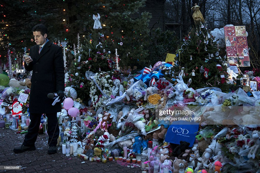 A TV reporter waits to do a standup report from a road side memorial dedicated to the victims of the shooting at Sandy Hook Elementary School December 18, 2012 in Newtown, Connecticut. Students in Newtown, excluding Sandy Hook Elementary School, return to school for the first time since last Friday's shooting at Sandy Hook which took the live of 20 students and 6 adults. AFP PHOTO/Brendan SMIALOWSKI