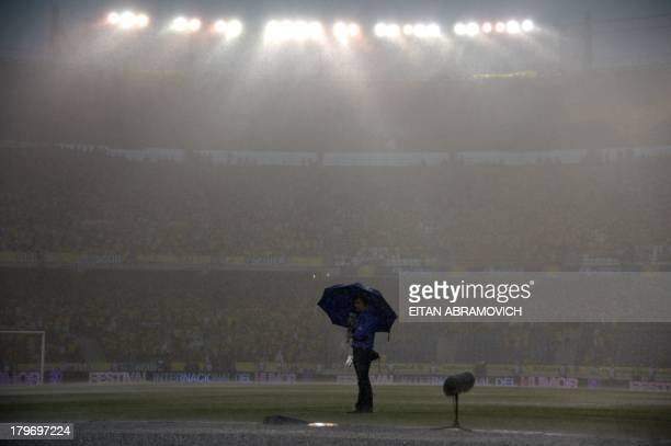 A TV reporter works under heavy rain before the start of the FIFA World Cup Brazil 2014 qualifying match between Colombia and Ecuador at the...