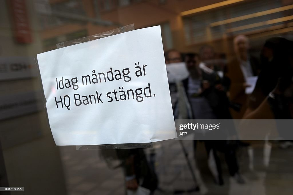 Reporters and photographers are reflected on the door of the Swedish investment bank HQ Bank in Stockholm on August 30, 2010, where a sign reads 'Today, Monday HQ Bank is Closed.' HQ Bank said on August 30 it was going into involuntary liquidation after the country's financial supervisory authority revoked all its licences. The bank said in a statement that efforts over the weekend to find a way to keep the bank operating had failed after the authority (Finansinspektionen, FI) on August 28 annonced it had revoked HB Bank AB's licence.