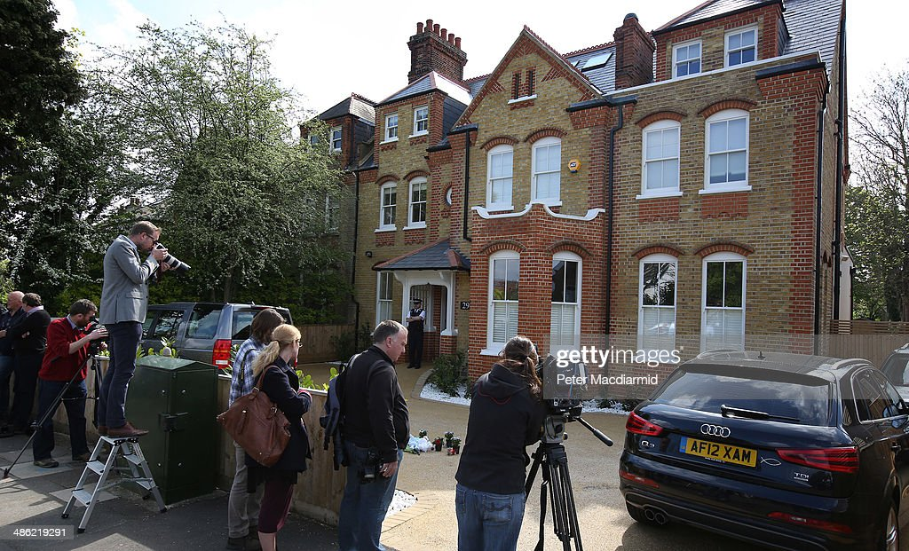 Reporters and photographers gather at a house in New Malden where the bodies of three children were found on April 23, 2014 in south London, England. Police say that a 43 year old woman has been arrested after the bodies of three children were found at a property last night.