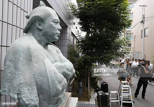 Reporters and photographers gather near a bronze statue of legendary sumo wrestler Chiyonofuji in front of the Kokonoe stable in Tokyo on Aug 1 a day...