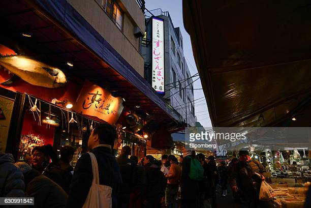 Reporters and visitors gather in front of the Sushi Zanmai restaurant in Tsukiji after the first auction of the year at Tsukiji Market in Tokyo Japan...