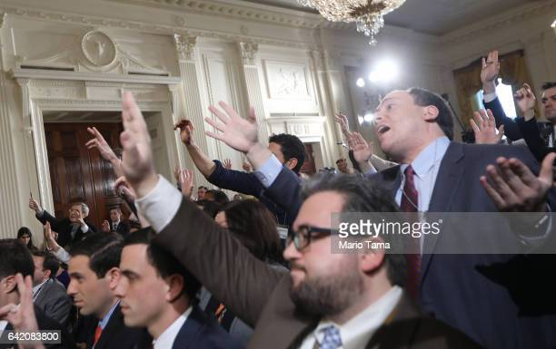 Reporters attempt to pose questions to US President Donald Trump during a news conference announcing Alexander Acosta as the new Labor Secretary...