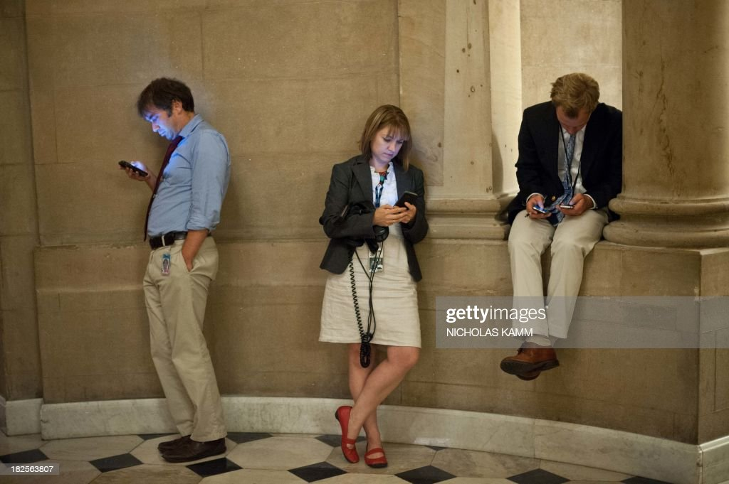Reporters check their smartphones while waiting outside US House Speaker John Boehner's office at the US Capitol in Washington on September 30, 2013 as a possible government shutdown looms. The United States stumbled to within hours of a government shutdown, as a budget duel between President Barack Obama and Republicans threatened America with a self-inflicted economic wound. AFP PHOTO/Nicholas KAMM