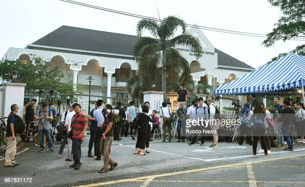 Reporters gather in front of a court near Kuala Lumpur on April 13 at which proceedings will be held for two women indicted for killing Kim Jong Nam...
