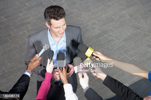 Reporters holding microphones for politician : Stock Photo