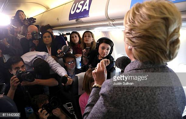 Reporters look on as democratic presidential nominee former Secretary of State Hillary Clinton speaks aboard her campaign plane at Chicago Midway...