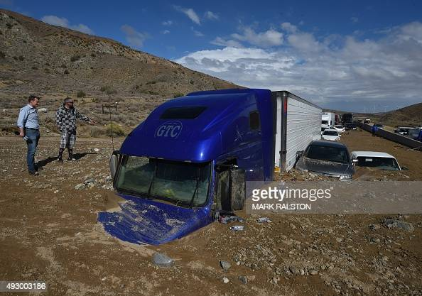 Reporters look vehicles stuck on a road after being trapped by a mudslide on California Highway 58 in Mojave California on October 16 after...