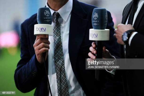 Reporters of Qatar's AlJazeera owned television channel BeIN Sports are seen holding their microphones with the channel's logo prior to the French L1...