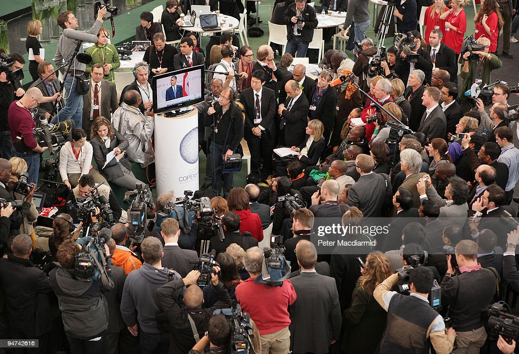 Reporters, photographers and television crews gather round a TV monitor to listen as US President Barack Obama address delegates at the final day of the UN Climate Change Conference on December 18, 2009 in Copenhagen, Denmark. World leaders will try to reach agreement on targets for reducing the earth's carbon emissions on this last day of the summit.