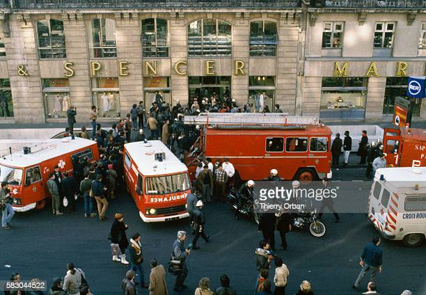 Reporters police and bystanders gather around the ambulances and fire trucks after a terrorist attack on the Marks Spencer department store on Rue...