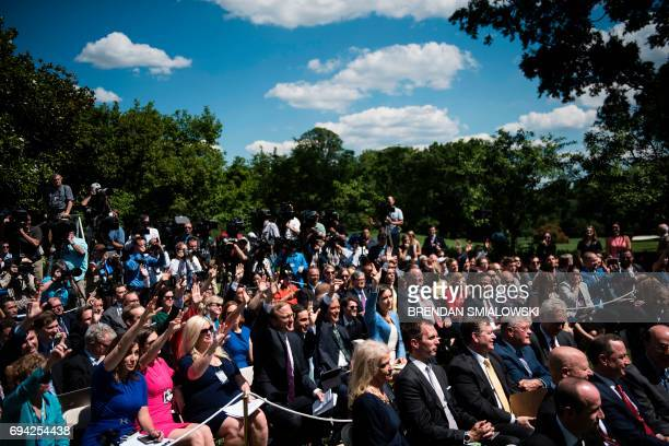Reporters raise their hands to ask questions of US President Donald Trump and Romania's President Klaus Iohannis during a press conference in the...