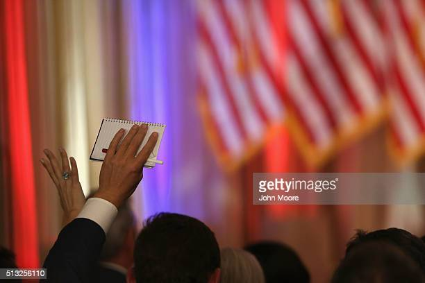 Reporters raise their hands to question Republican Presidential frontrunner Donald Trump at his MarALago Club on Super Tuesday March 1 2016 in Palm...