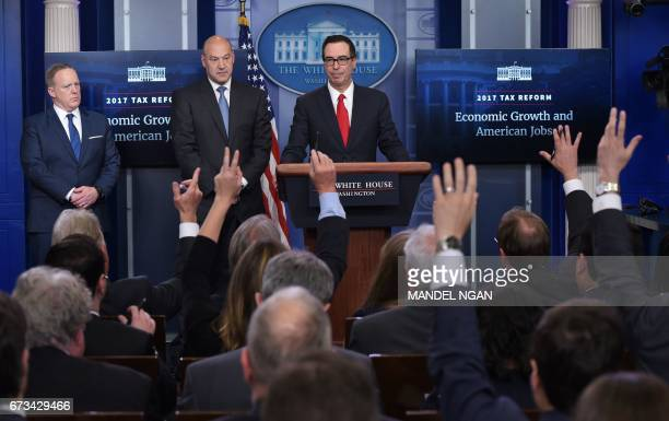 Reporters raise their hands with questions for Treasury Secretary Steven Mnuchin and Chief Economic Advisor Gary Cohn watched by White House Press...