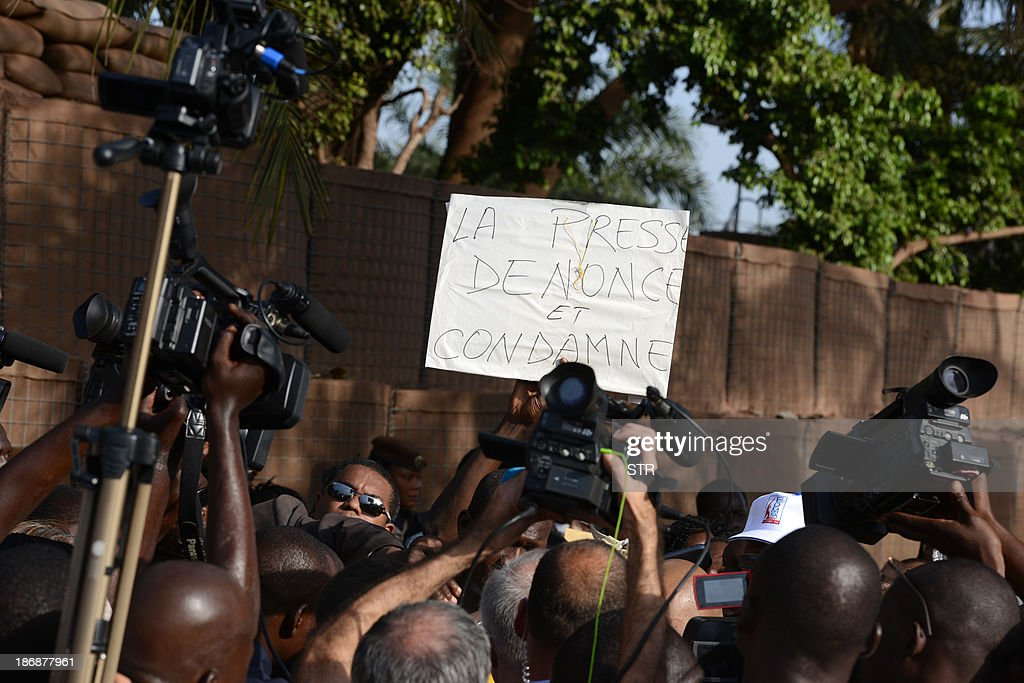 Reporters raise their video cameras to film while Malian journalists are holding a placard in French reading 'Press denounces and condemns' during a white march on November 4, 2013 in Bamako, in memory of Radio France Internationale (RFI) journalist Ghislaine Dupont and sound technician Claude Verlon killed in the town of Kidal. French troops were working today with Malian security forces to hunt the killers of the two French journalists shot dead in the west African nation's rebel-infested northern desert. Ghislaine Dupont, 57, and Claude Verlon, 55, were kidnapped and killed by what French Foreign Minister Laurent Fabius said were 'terrorist groups' in the flashpoint northeastern town of Kidal on November 2, 2013. AFP PHOTO / STR