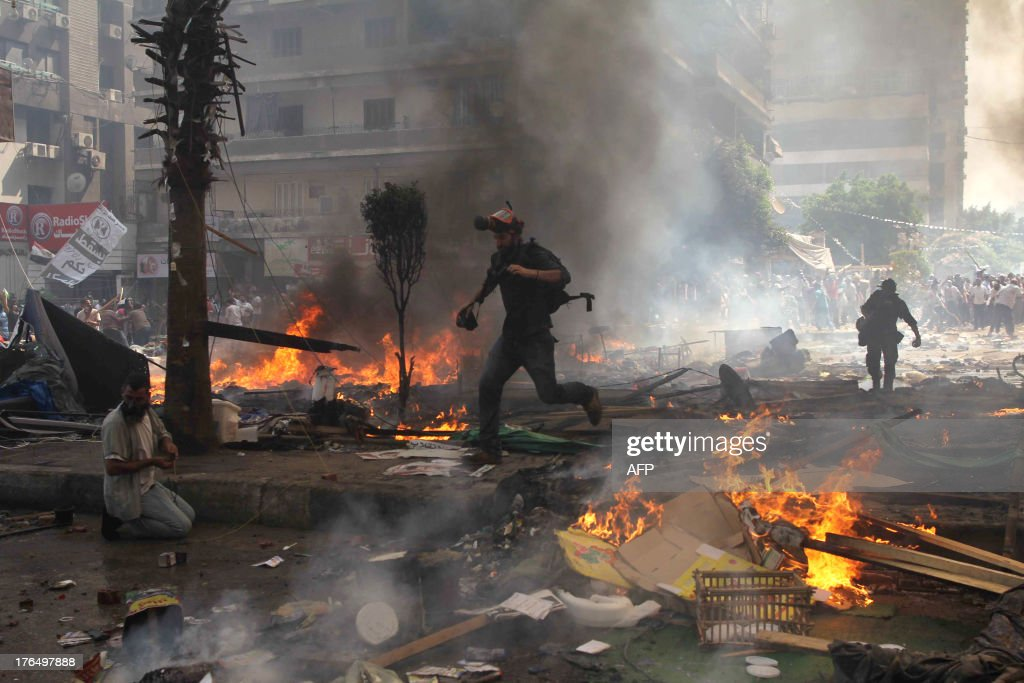 Reporters run for cover during clashes between Muslim Brotherhood supporters of Egypt's ousted president Mohamed Morsi and police in Cairo on August...