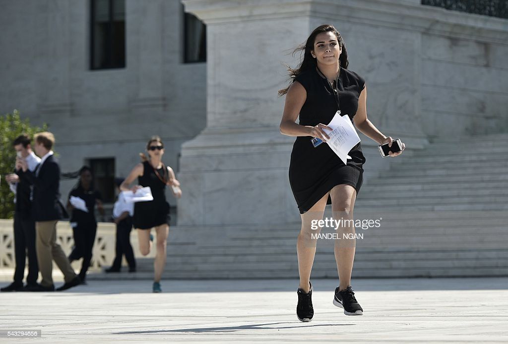 Reporters run out of the US Supreme Court after a ruling striking down a Texas law placing restrictions on abortion clinics, outside of the Supreme Court on June 27, 2016 in Washington, DC. In a case with far-reaching implications for millions of women across the United States, the court ruled 5-3 to strike down measures which activists say have forced more than half of Texas's abortion clinics to close. / AFP / MANDEL