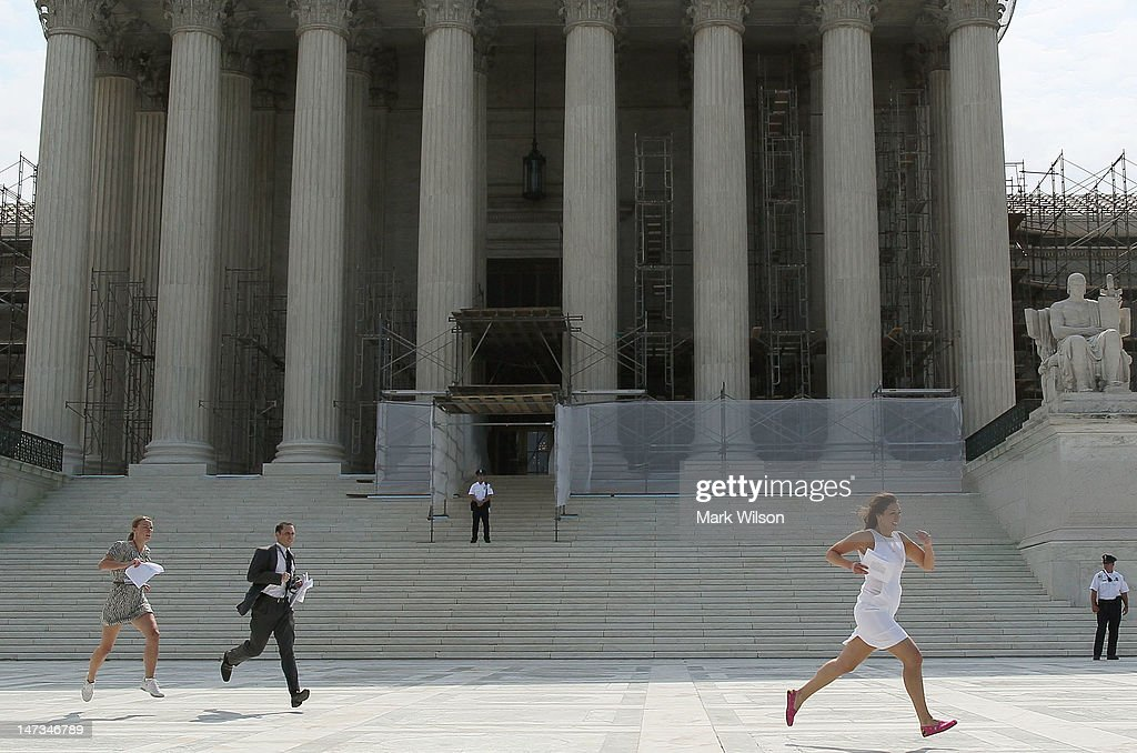 Reporters run with the U.S. Supreme Court's health care decision on June 28, 2012 in Washington, DC. Today the high court upheld President Obamas health care overhaul, in a victory for the president and Congressional Democrats.
